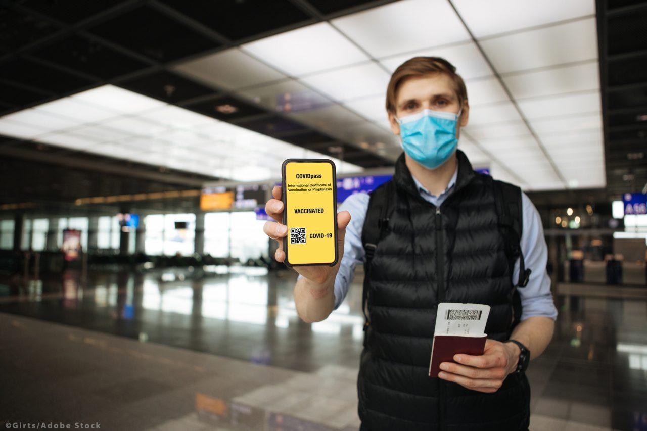 Digital vaccine passport. Hand holding mobile COVID-19 app for v